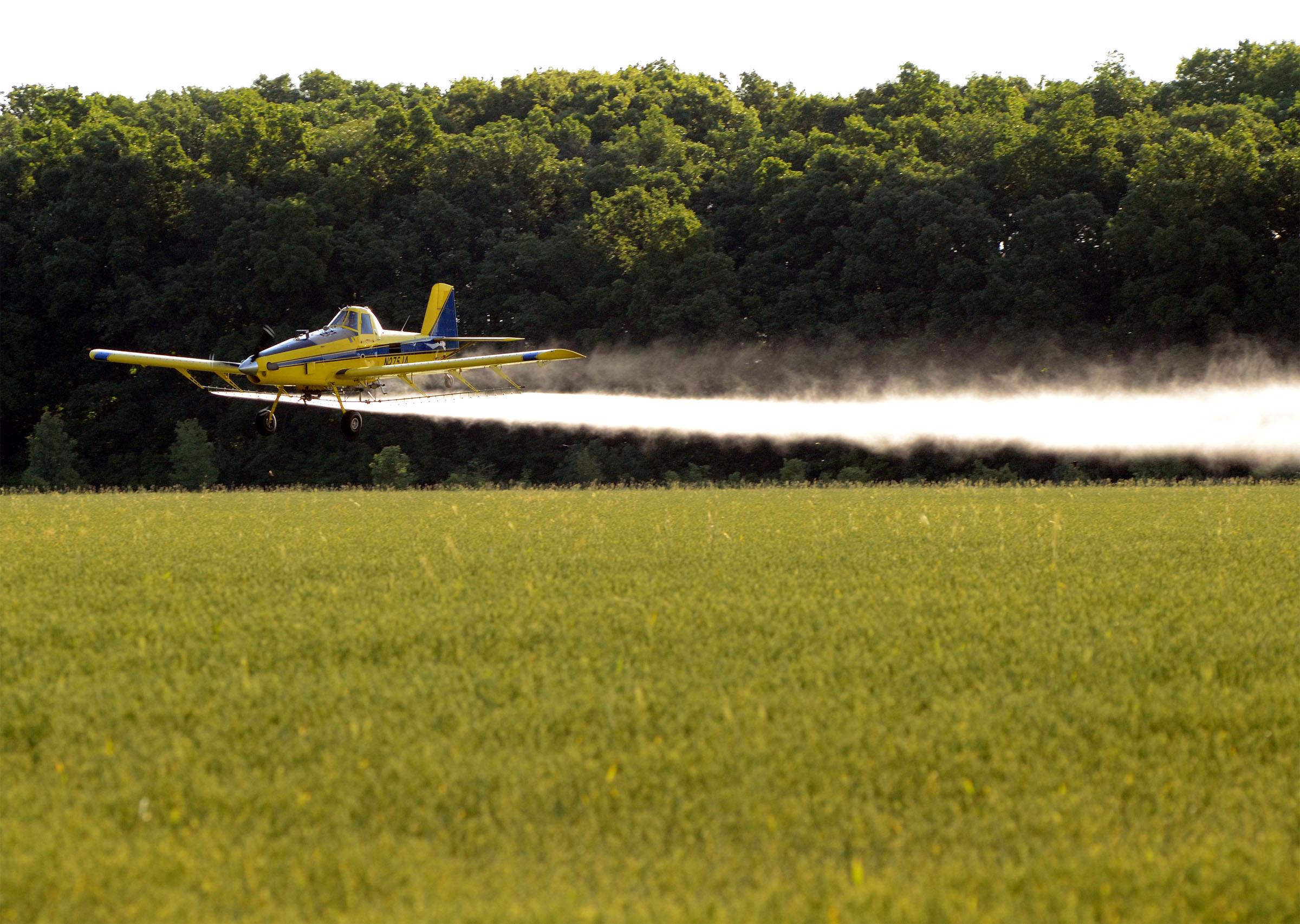 A crop-duster plane is spotted flying low as it sprays a field of wheat in Jerusalem Township. (Press photo by Ken Grosjean)