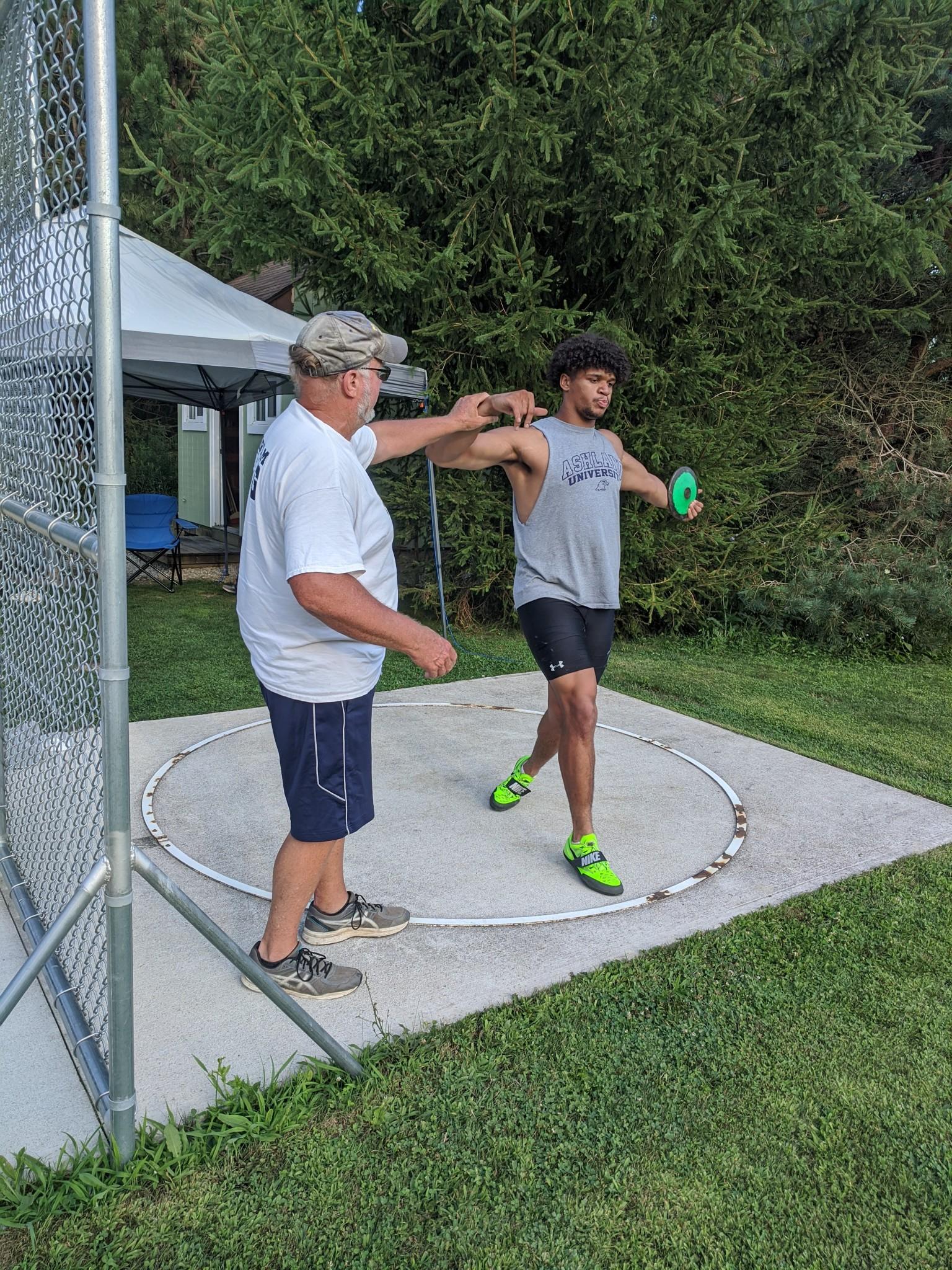 Coach Mike Pendleton working with Ashland University thrower Noah Koch (Genoa). (Photo courtesy Mike Pendleton)