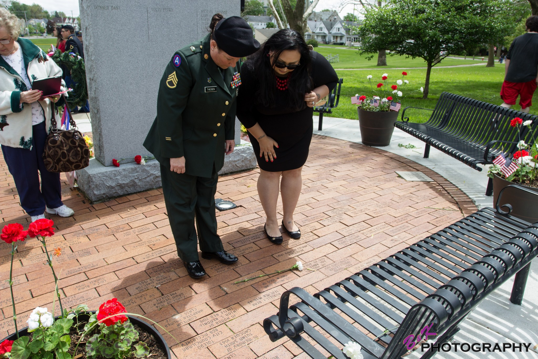 "Gold Star Wife Veronica Mora and SSGT Susan Theisen place a carnation on the memorial brick placed in memory of Sgt. Arthur Mora Jr., killed in action in Operation Iraqi Freedom on Oct. 19, 2005.  (Photo courtesy of B &amp; K Photo/<a href=""http://www.facebook.com/BKphotovideo"">www.facebook.com/BKphotovideo</a>)"