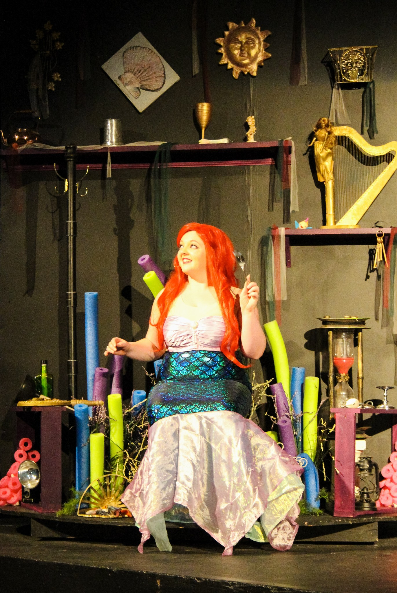 "Ariel (Leslie Childers) in her grotto with her ""new"" dinglehopper in Fremont Community Theatre's production of Disney's ""The Little Mermaid."" (Photo by Lynne Wagner)"