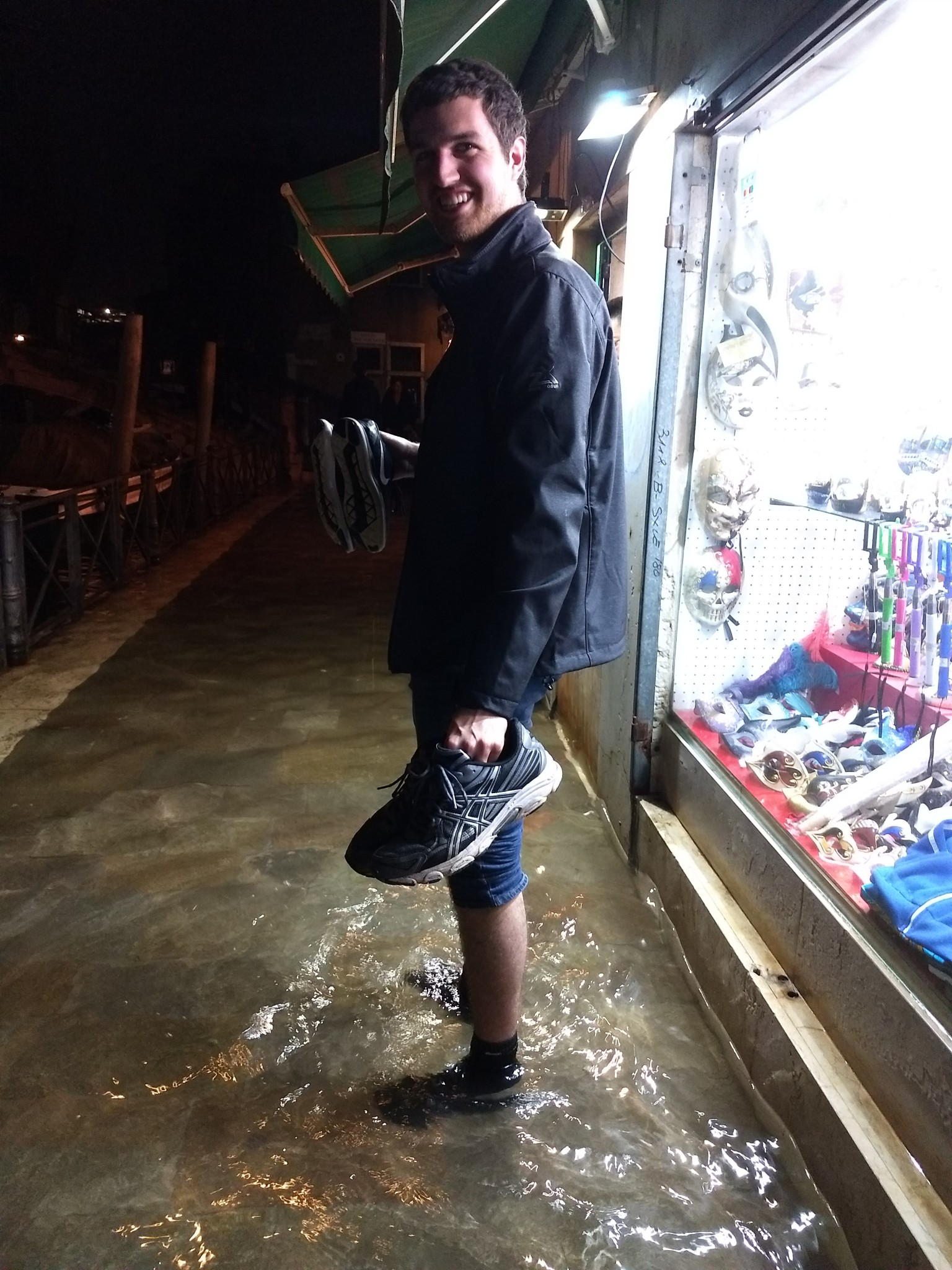 Caught in acqua alto (high tide), the author's fiance, Tyler, carries their shoes as they navigated several inches of flood water from the canals to their hotel. (Photo by Katie Siebenaller)