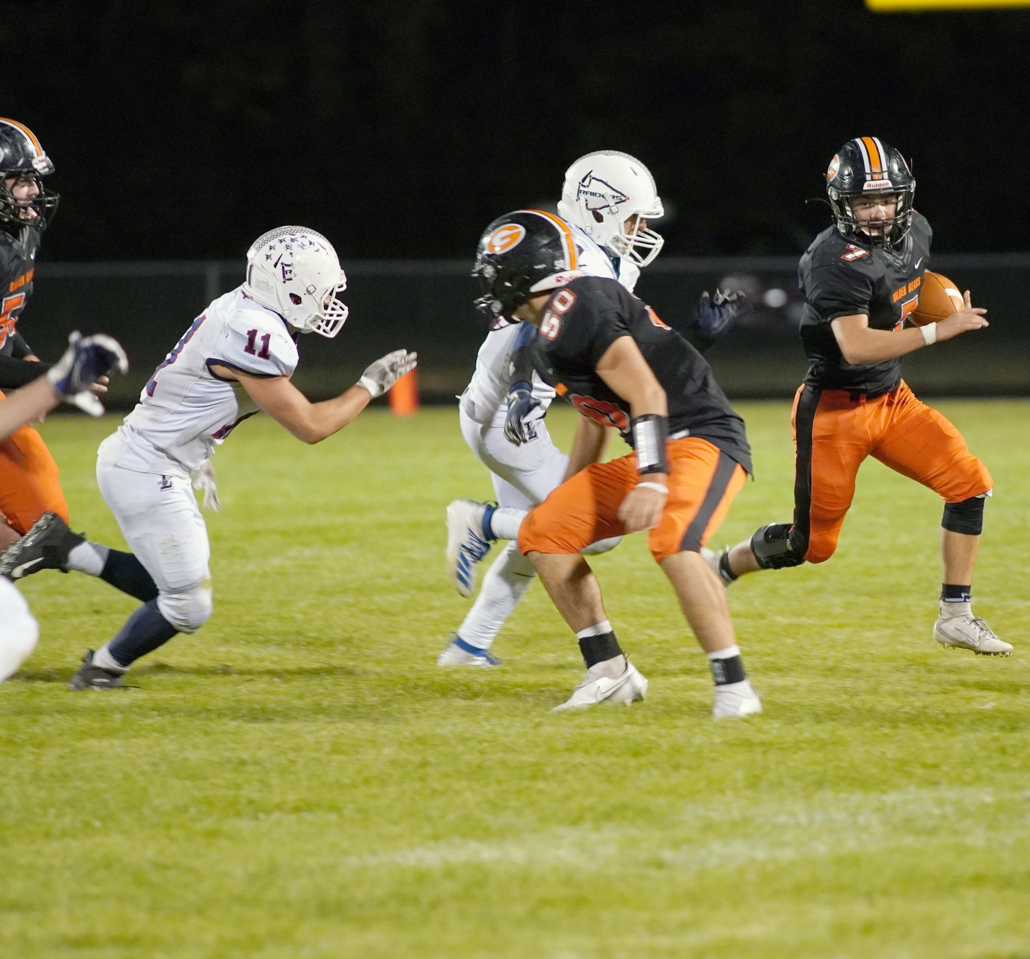 Gibsonburg junior Tyler Schooley (50), a 5-foot-11, 195-pound offensive guard, looks to block an opposing defender so senior halfback Phillip Davies (7) can find running room. (Photo by Jeff Holcomb)