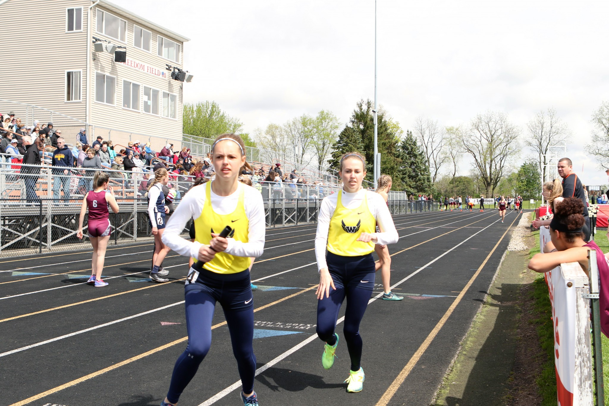 Anchor leg Ava Beam takes the baton from Woodmore teammate Olivia Thatcher. (Press photo by Lee Welch/FamilyPhotoGroup.com)