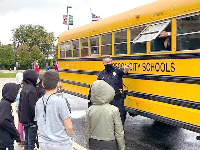 "Oregon Police Officer Ted Moore took a few moments last week to remind Coy Elementary students of the importance of following school bus safety rules. With many new health and safety measures in place this school year due to COVID-19, Officer Moore felt it was important to reinforce some of the ""old rules"" designed to keep students safe as they travel to and from school. (Oregon Police photo)"