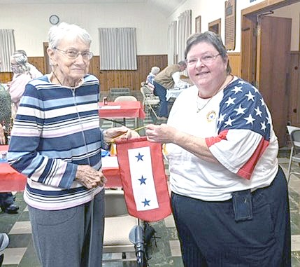 Troy-Webster American Legion Auxiliary President Becky Dippman, right, presents 60-year member Geraldine Levorchick, left, a Blue Star Banner with three stars, in honor of her three great-grandsons who are currently serving in the military.