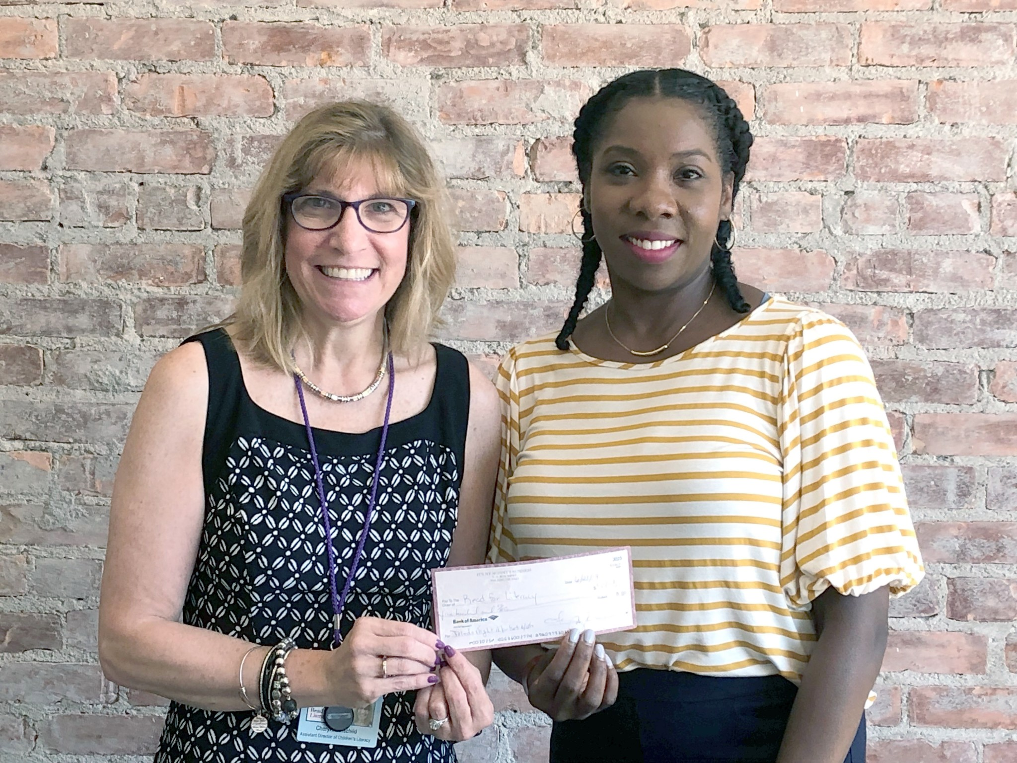 Fancy Moreland (right), creator of Toledo Night Market, presents a donation check to Cheryl Rothschild, Director of Volunteers and Library Outreach at Read for Literacy. (Submitted photo)