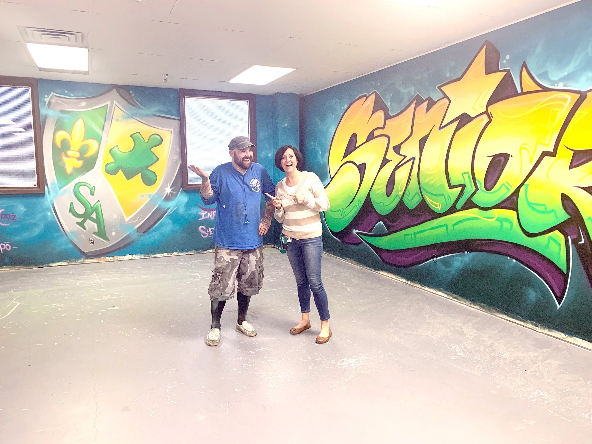Graffiti artist Tony Touch joins Summit Academy Toledo principal Dawn Heck in front of freshly finished wall art that transformed a section of the school into a senior lounge. (Submitted photo)