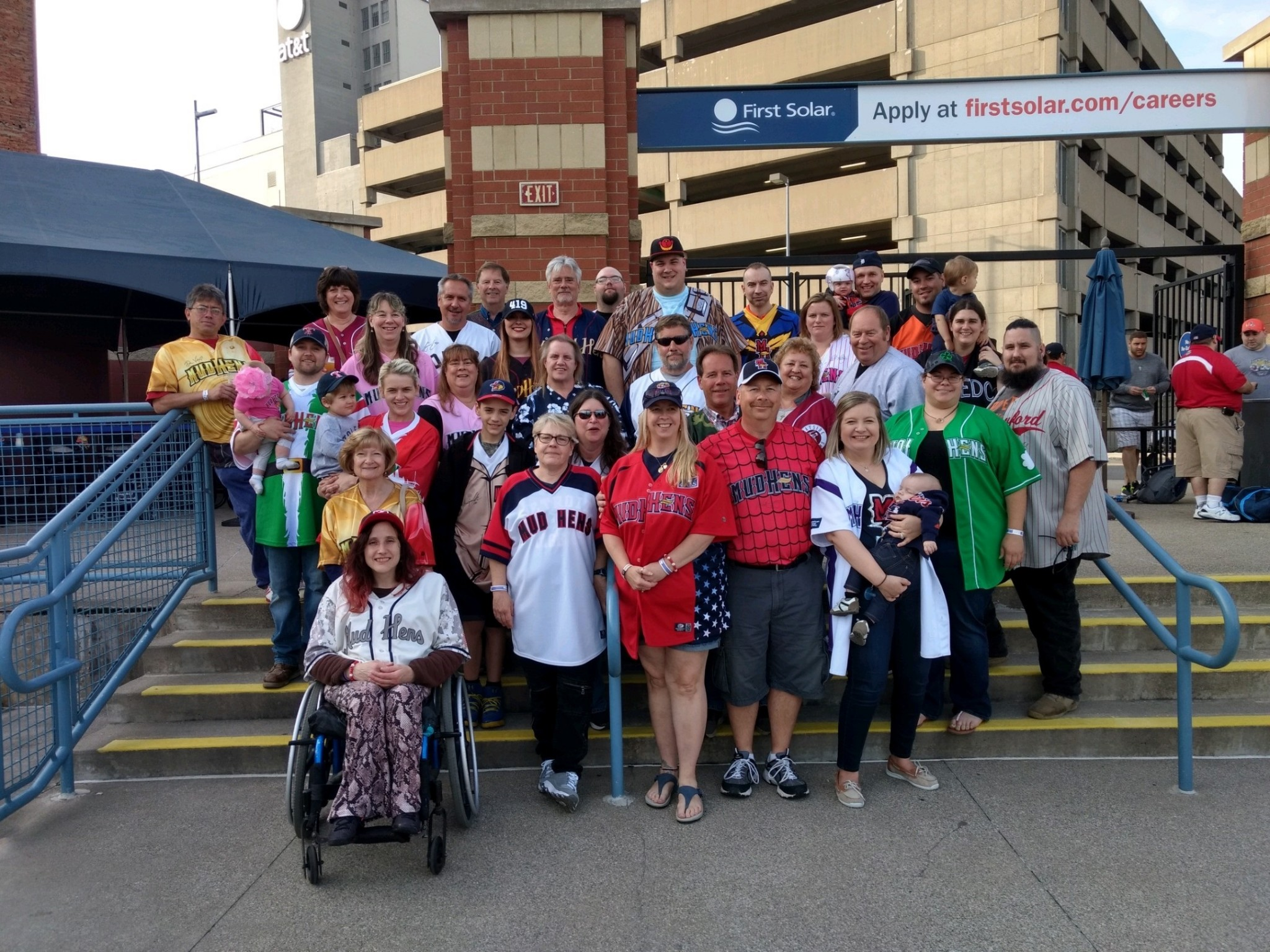"Beth Jaegly, front row, third from right, and her husband, Scott, standing next to her, second from right, turned a night at the ball game with family and friends into a ""party with a purpose,"" raising funds for Family House. (Submitted photo)"