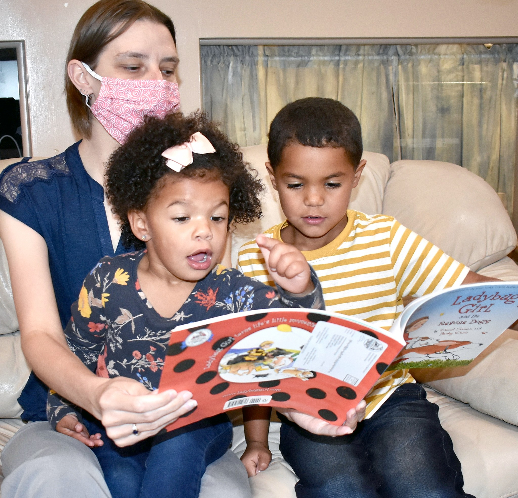 April Schalk, Office Manager of United Way in Ottawa County, reads an Imagination Library book to young family friends, Ellieyonna (2) and Eric (4) Buckley. (Submitted photo)