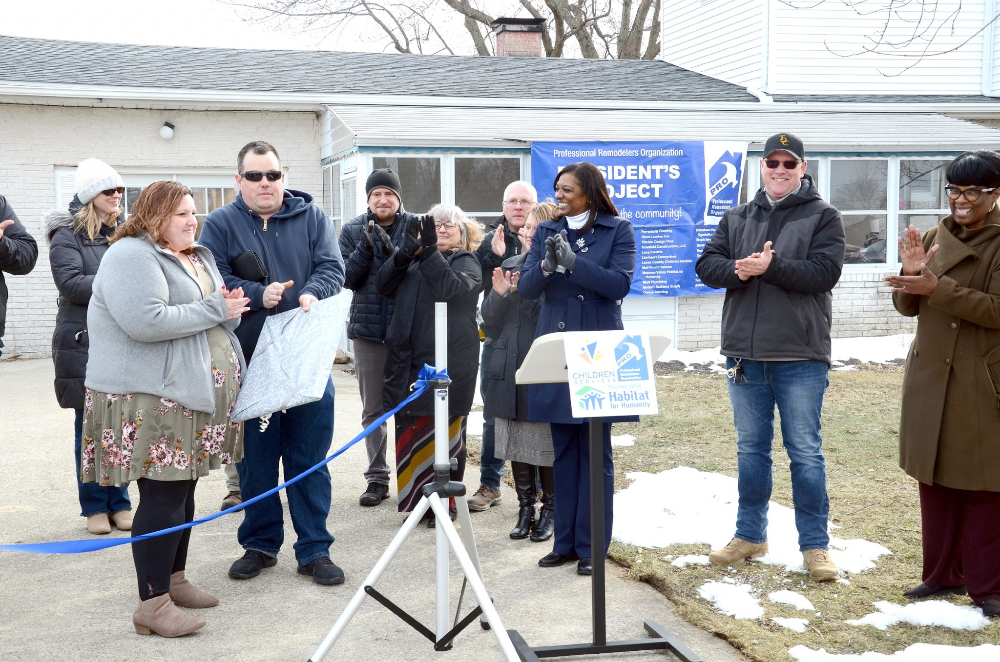 It was applause all around at the ribbon-cutting of a 300-square-foot addition to the Jerusalem Township home of Malori and Chad McCloskeys, who are Lucas County Children Services foster parents. The project, a donation-driven, volunteer effort coordinated by Professional Remodelers Organization (PRO) and Habitat for Humanity, will help the McCloskeys foster more children, in particular, sibling groups. (Press photo by Ken Grosjean)