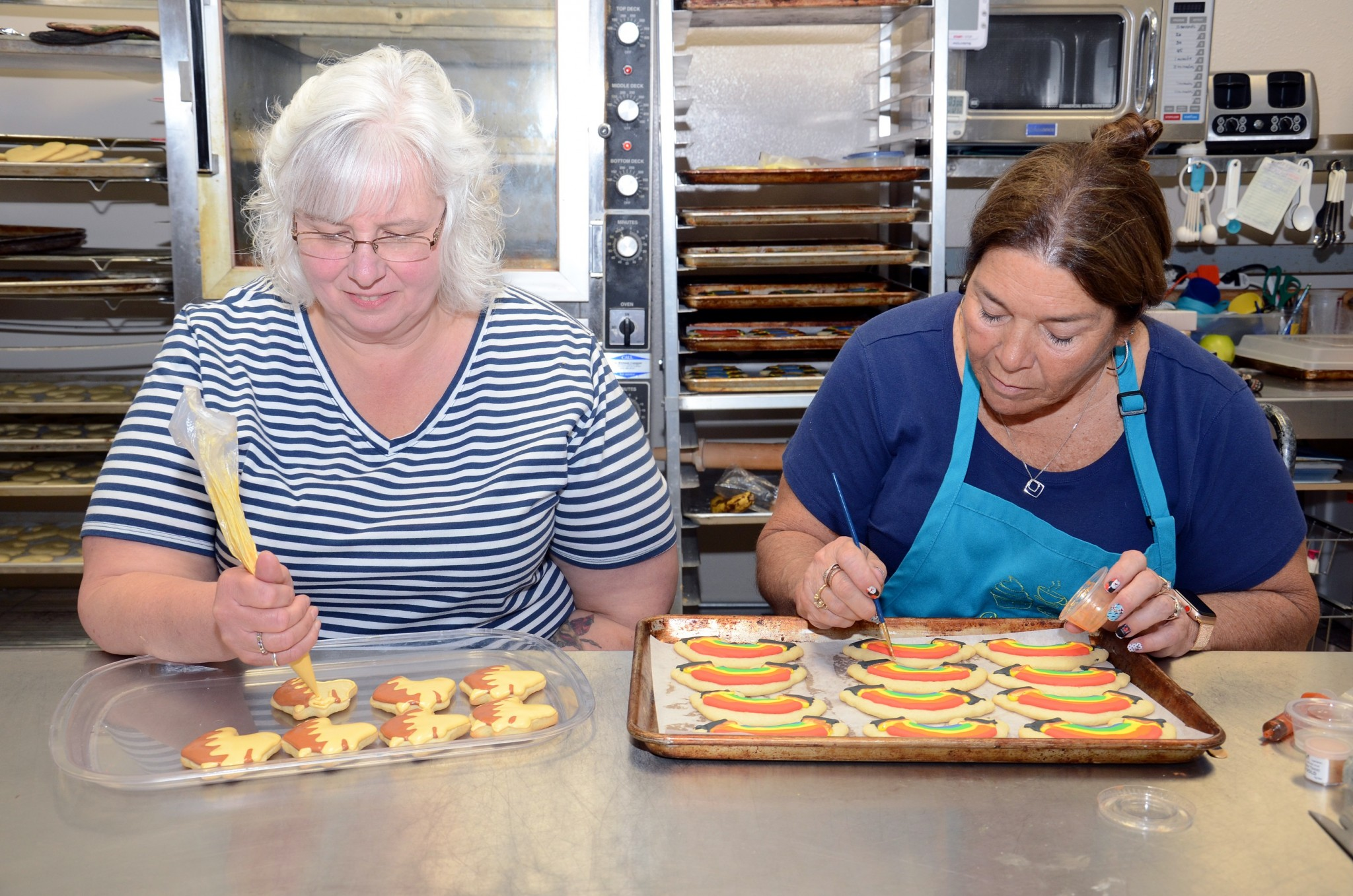 Lisa White and Nancy Calverto work on special cookie orders at Patty Cakes, Oak Harbor. (Press photo by Ken Grosjean)