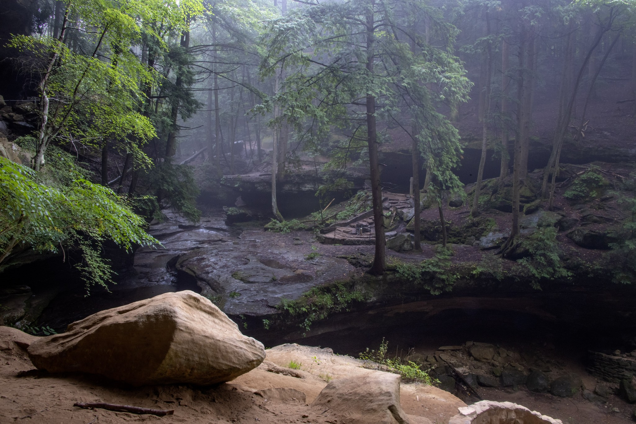 Fog settles into the gorge at Ash Cave, one of the popular scenic sites in the Hocking Hills State Park. As part of the effort to make the parks safer for visitors the two-way trail to and from Ash Cave has had a return loop added and the trail converted to one-way travel. The change minimizes contact with other visitors. Many of the park's one way trails have been modified with a return loop so they are one-way. (Photo by Art  Weber)