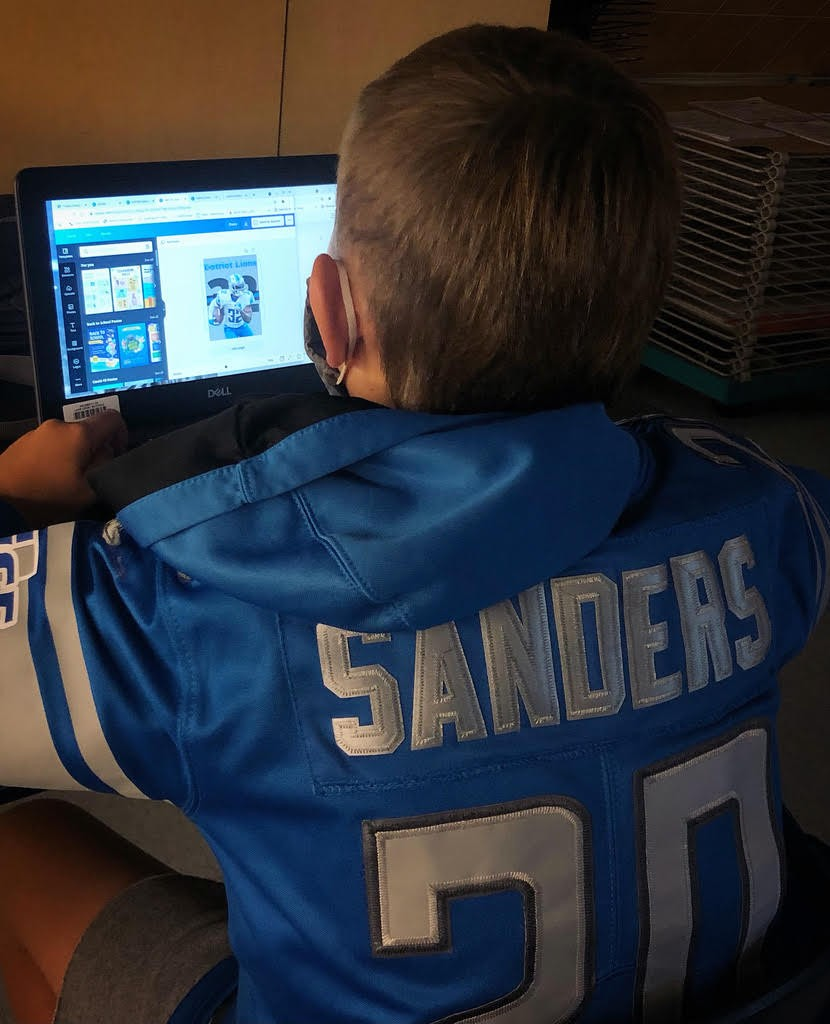 Lake Middle School student John Krift designing his poster in the new 7th grade Digital Art class. His poster design is for the Detroit Lions and he was dressed to match his artwork.  (Submitted photo)