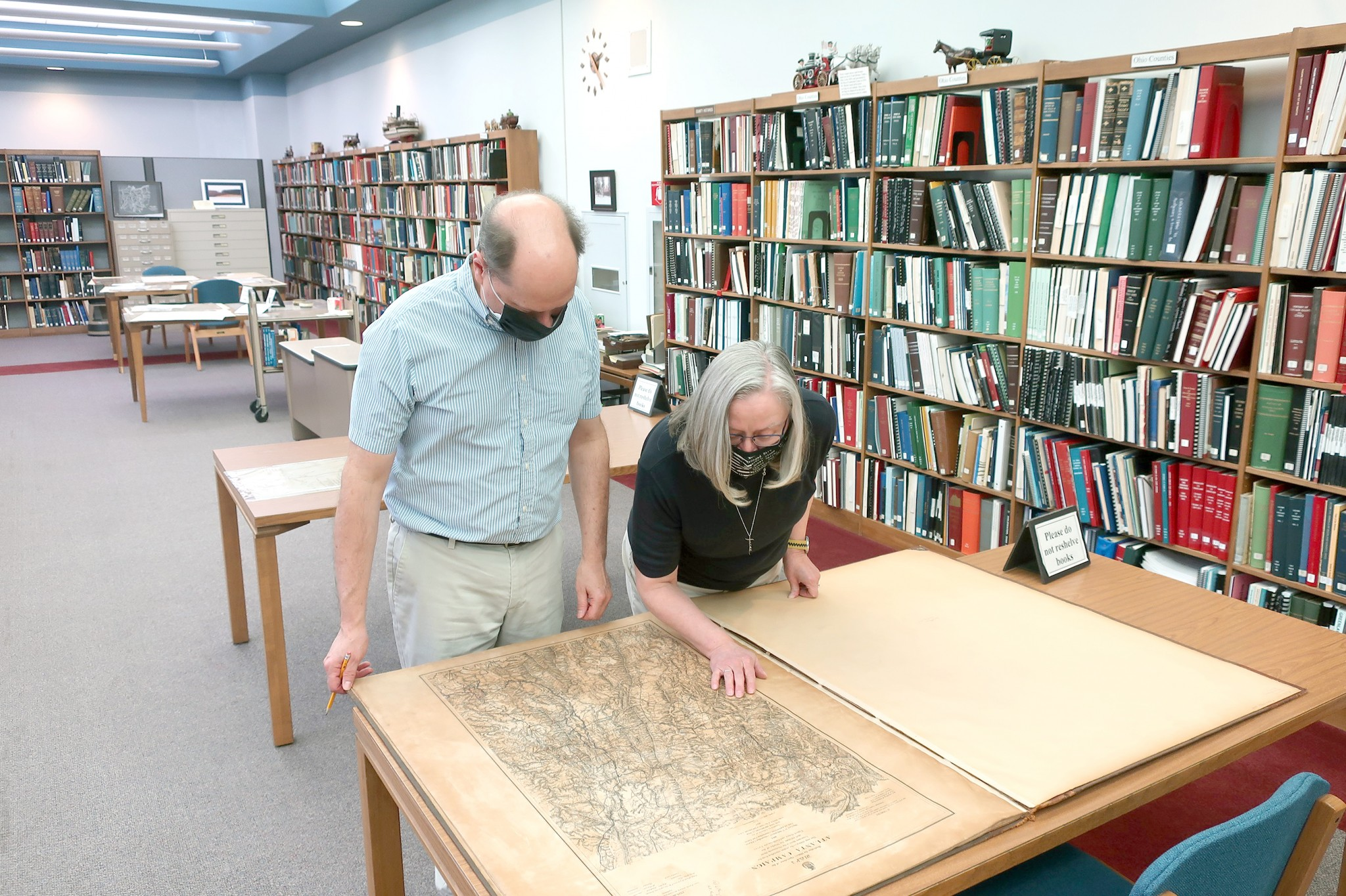 Head Librarian John Ransom, (left), and Librarian Pat Breno examine a book of historic maps of Civil War battles. This book is part of the map collections at the Hayes Presidential Library & Museums. (Submitted photo)