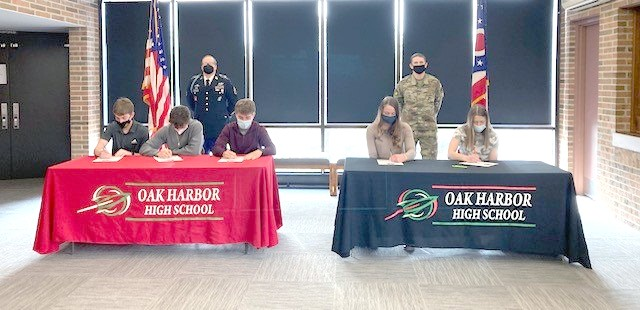 Left table, from left: Ryan Friar, Army ROTC; Joseph Perry, Marines and Eli Sherman, Army Reserves sign their commitments as Sgt. Blankenship - Army Military Recruiter looks on. Right table (from left): AunaTack, Ohio Air National Guard and Madison McKitrick, Ohio National Guard sign their commitments in front of Sgt. Gainer, Air National Guard Recruiter. (Submitted photo)