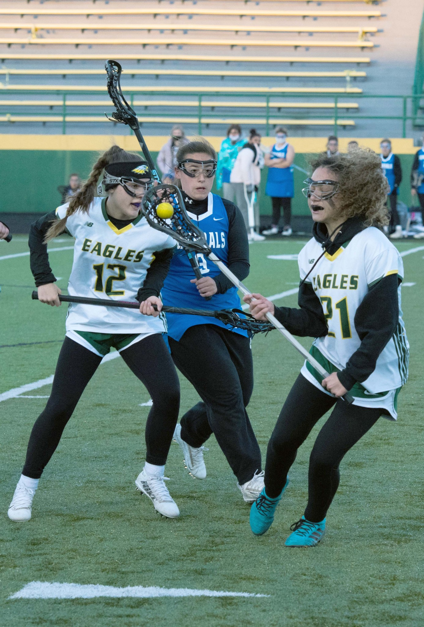 """Clay junior attack Hannah Haas (12) and freshman midfielder Kendra Stevens (21) try to fend off an Anthony Wayne defender. (Press photo by Russ Lytle/<a href=""""http://www.Facebook.com/RussLytle/RHP"""">www.Facebook.com/RussLytle/RHP</a>)"""