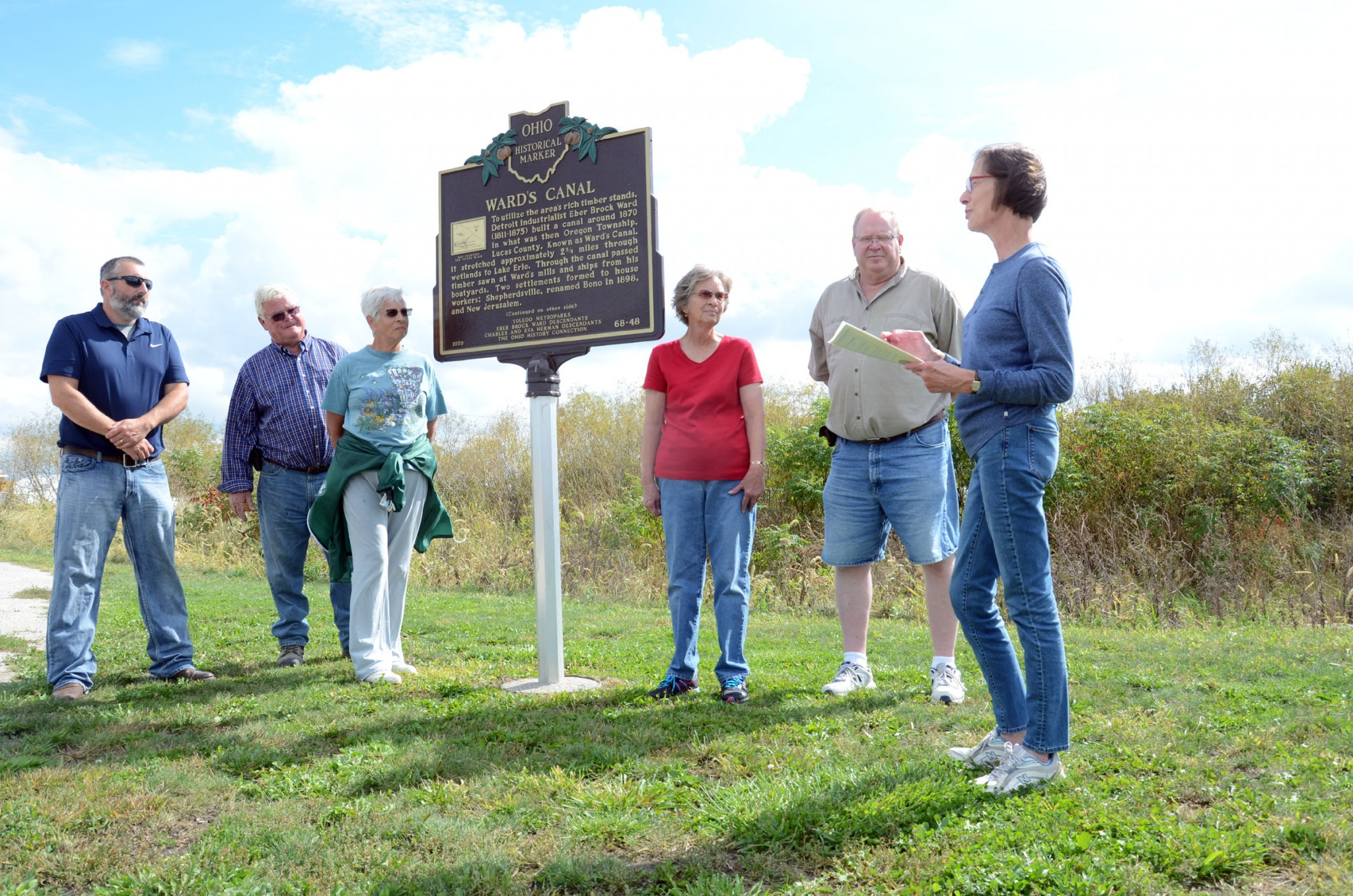 Pictured, left to right: Beau Miller, Dave Bench, Jerusalem Township Trustees; Deanna Restemyer, Rosemary Brim and Bill Miller listen as Debbie Miller dedicates the Ohio Historical Marker for Ward's Canal at Howard Marsh Metropark. Restemyer and Brim are sisters, and Bill Miller is husband to Debbie Miller. (Press photo by Ken Grosjean)