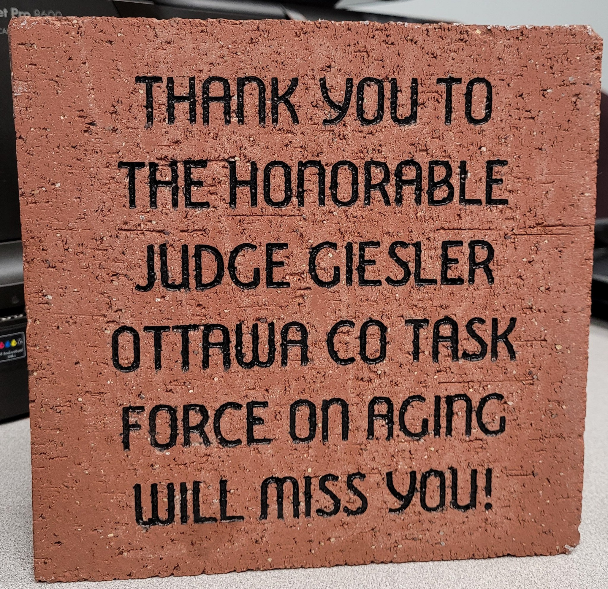 """Ottawa County Task Force on Aging honored Ottawa County Juvenile/Probate Judge Kathleen Giesler for her leadership in developing the organization by presenting her with a paver, to be set at the county fairgrounds. The paver says, """"We will miss you!"""" since Judge Giesler is retiring Feb 8. (Submitted photo)"""