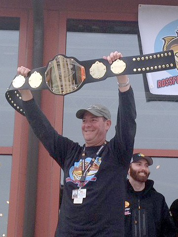 Bass Pro Manager Scott Liebert holding up the belt that the winning team receives at the Rossford Walleye Roundup. (Photo courtesy Julianne Jardine/Public Relations Assistant/Rossford Convention and Visitors Bureau)